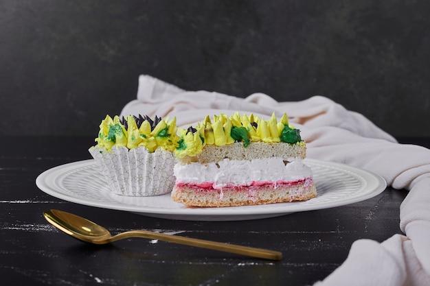 白いプレートにひまわり風の装飾が施されたケーキ。 無料写真