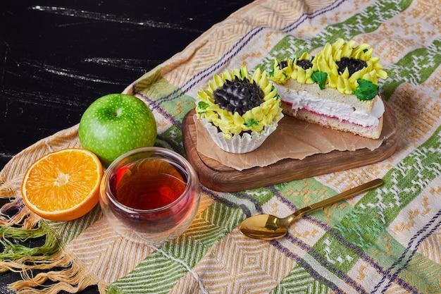 お茶と木の板にひまわり風の装飾が施されたケーキ。 無料写真