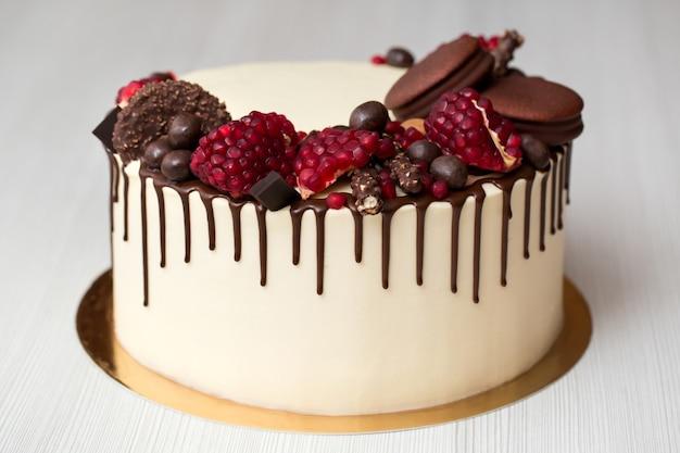 Торт с гранатовыми орехами и шоколадным декором из белого сливочного шоколада Premium Фотографии