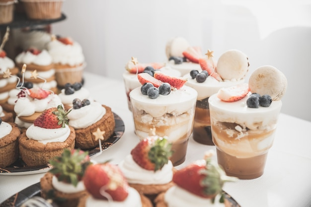 Cakes and muffins with cream and berries. sweets, candy, buffet. dessert table . party reception, decorated in restaurant. candy bar Premium Photo