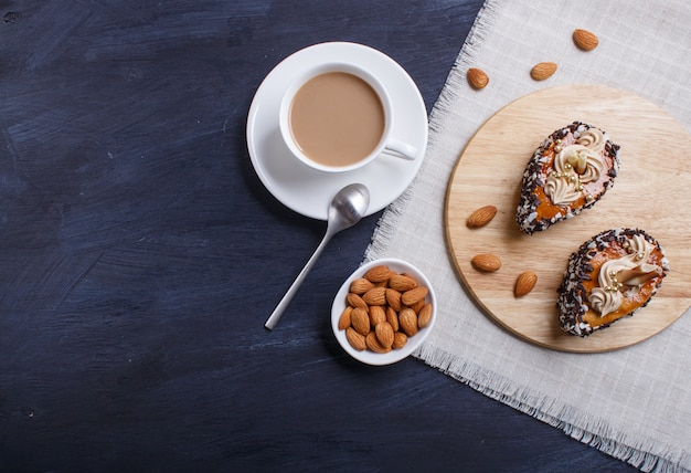 Cakes with chocolate chips  and cream decorations  on wooden board on black wooden. Premium Photo