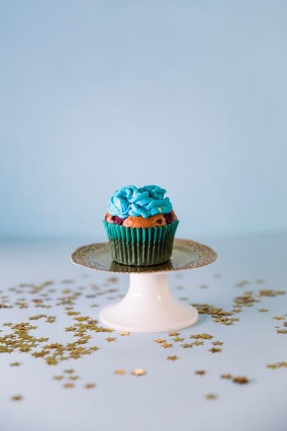 金色の星は青い背景にcakestandの新鮮なおいしい誕生日ケーキの上に広がる 無料写真