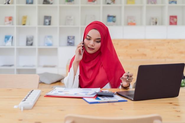 赤いヒジャーブを着て、calculator.businessと金融、オフィスの机、経済、会計上のラップトップで働く若いイスラム教徒ビジネス女性会計士 Premium写真