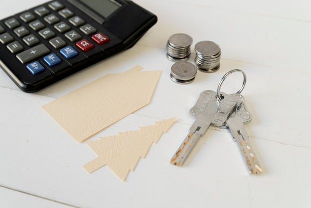 Calculator; coins stack; keys with house and tree paper cutout on white wooden table Free Photo