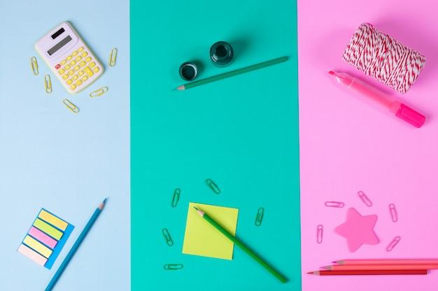 Calculator, color pencil, paper clip, on pastel green, pink, blue paper background Premium Photo