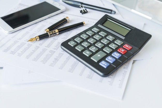 Calculator on desk with documents and smartphone Free Photo