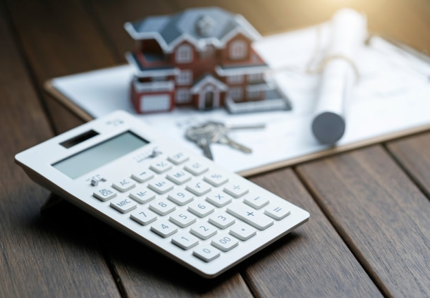A calculator in front of a villa house model with a blueprint Free Photo