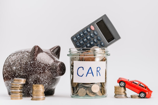 Calculator on glass coins jar with coin stack; car and piggybank against white background Free Photo