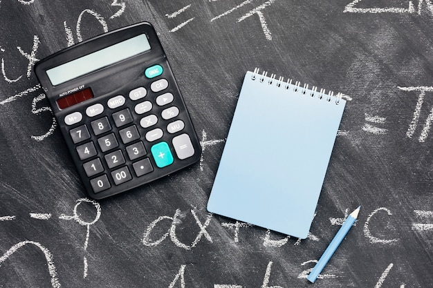 Calculator and notebook on chalkboard Free Photo