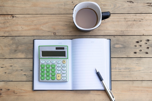 Calculator,notebook,coffee cup,pen on wooden background Premium Photo