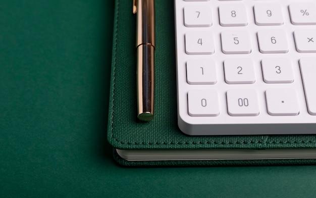 緑のテーブルとペンでノートの電卓。会計士の職場。 Premium写真