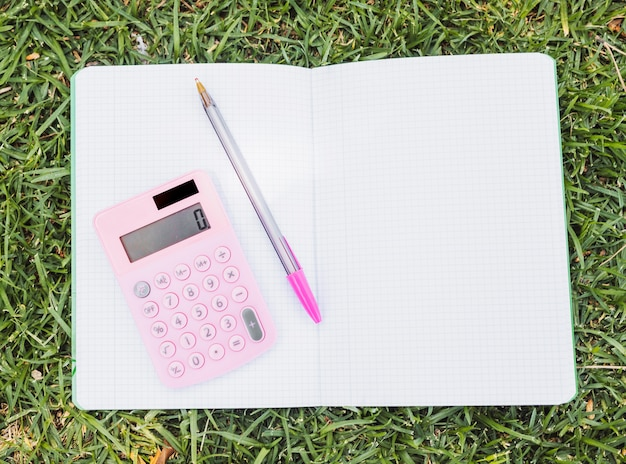 Calculator and pen on top of opened notebook Free Photo