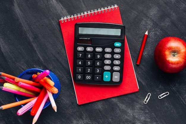 Calculator and stationery at blackboard Free Photo