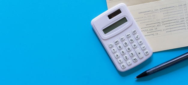 Calculator with bank account passbook and pencil on blue color background Premium Photo