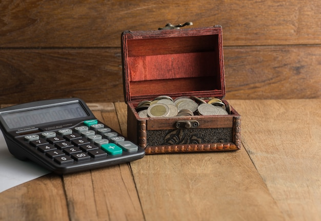 Calculator with coin in a coffer on wood background Premium Photo