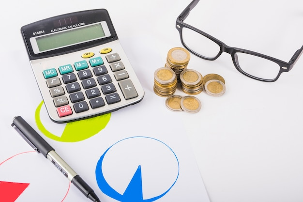 Calculator with coins stacks on table Free Photo
