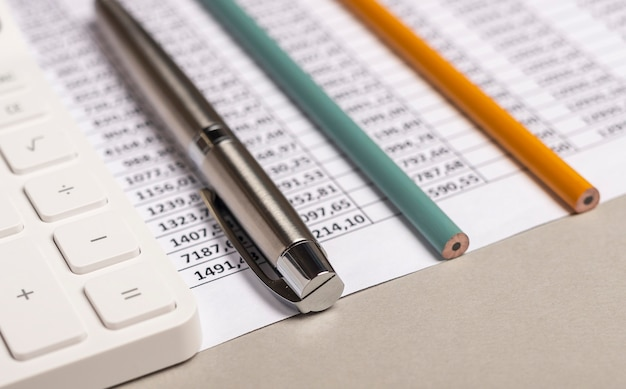 テーブルの上に財務書類とペンを持つ電卓をクローズアップ。会計士の職場。 Premium写真