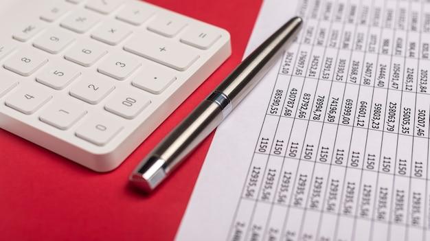 ペンで赤いテーブルに財務書類と電卓。会計士の職場。 Premium写真