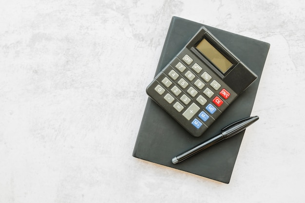 Calculator with notebook on table Free Photo