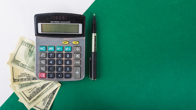 Calculator with paper money on table Free Photo