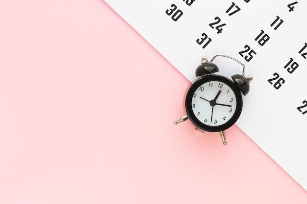 달력 및 분홍색 배경에 알람 시계입니다. 마감일, 비즈니스 회의 또는 여행 계획 개념 계획. 복사 공간이있는 평면 위치, 평면도. 프리미엄 사진