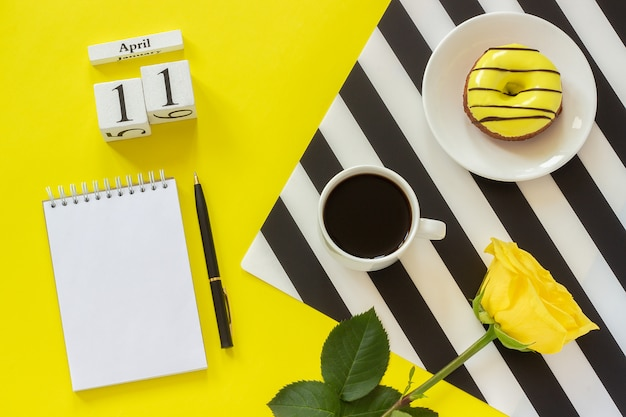 Calendar april 11th. cup of coffee, donut, rose, notepad. concept stylish workplace Premium Photo