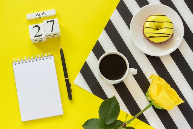 Calendar april 27th. cup of coffee,donut and rose, notepad for text. concept stylish workplace Premium Photo