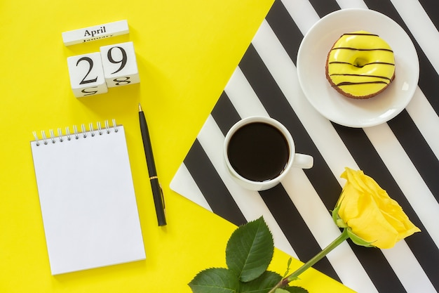 Calendar april 29th. cup of coffee,donut and rose, notepad for text. concept stylish workplace Premium Photo