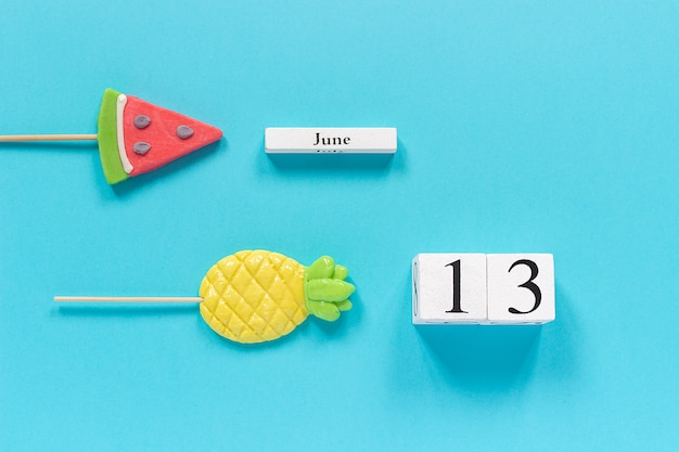 Calendar date june 13th and summer fruits candy pineapple, watermelon lollipops. Premium Photo