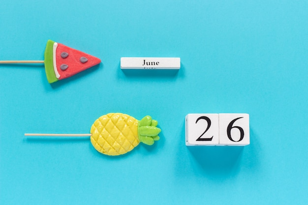 Calendar date june 26th and summer fruits candy pineapple, watermelon lollipops Premium Photo