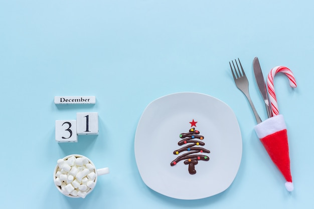 Calendar december 31st. sweet chocolate christmas tree on plate, cutlery, cup of cocoa Premium Photo