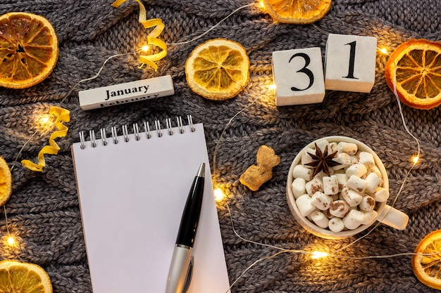 Calendar january 31st cup of cocoa and empty open notepad Premium Photo