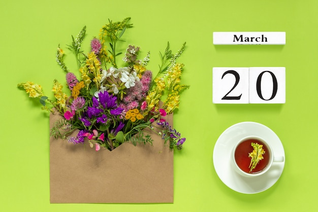 Calendar march 20. cup of herbs tea, kraft envelope with flowers on green background Premium Photo