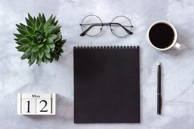 Calendar may 12. black notepad, cup of coffee, succulent, glasses on marble Premium Photo