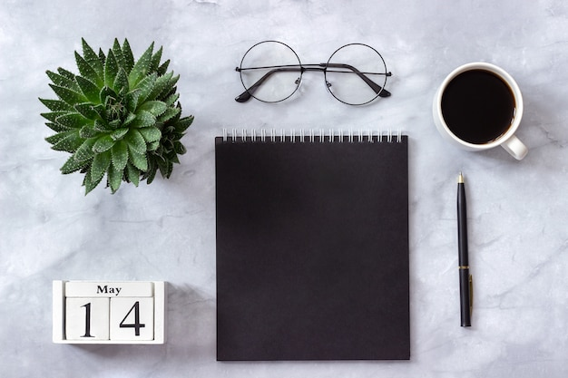 Calendar may 14. black notepad, cup of coffee, succulent, glasses on marble Premium Photo