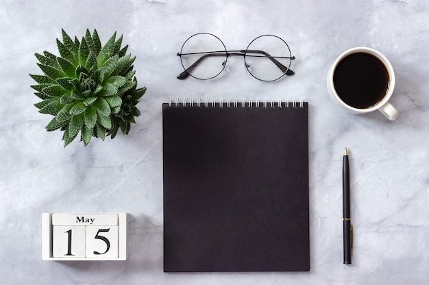 Calendar may 15. black notepad, cup of coffee, succulent, glasses on marble Premium Photo