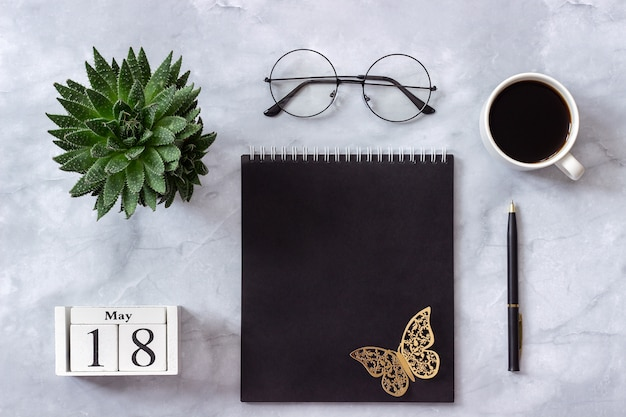 Calendar may 18. black notepad, cup of coffee, succulent, glasses on marble Premium Photo