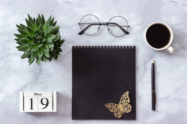 Calendar may 19. black notepad, cup of coffee, succulent, glasses on marble Premium Photo