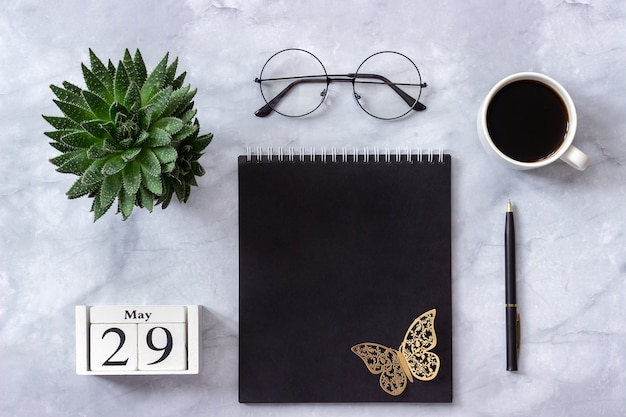 Calendar may 29. black notepad, cup of coffee, succulent, glasses on marble Premium Photo