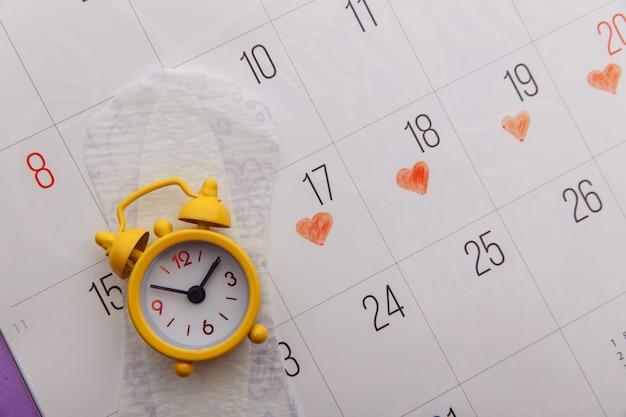 カレンダー、生理用ナプキン、黄色の目覚まし時計のクローズアップ。 Premium写真