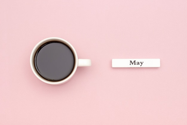 Calendar month may and cup of black coffee on pastel pink paper background. Premium Photo