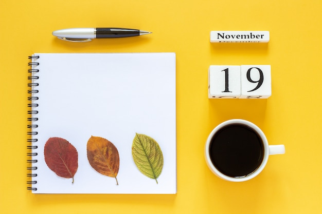 Calendar november 19 cup of coffee, notepad with pen and yellow leaf on yellow background Premium Photo