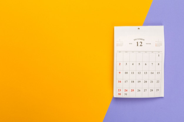 Calendar page on bright bicolor surface, top view Premium Photo