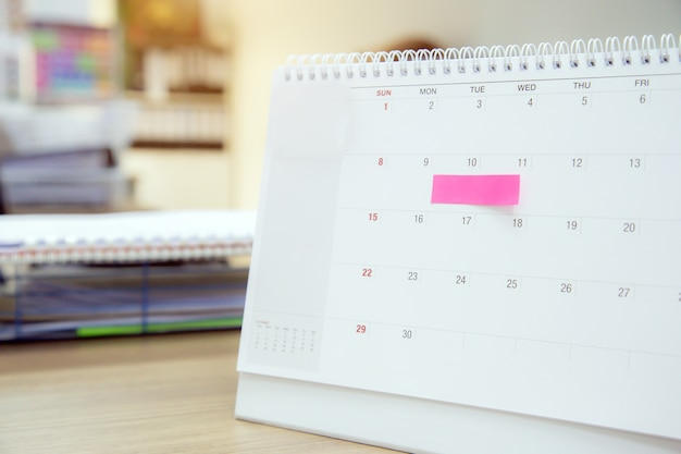 Calendar with paper note message on office desk for events planner. Premium Photo