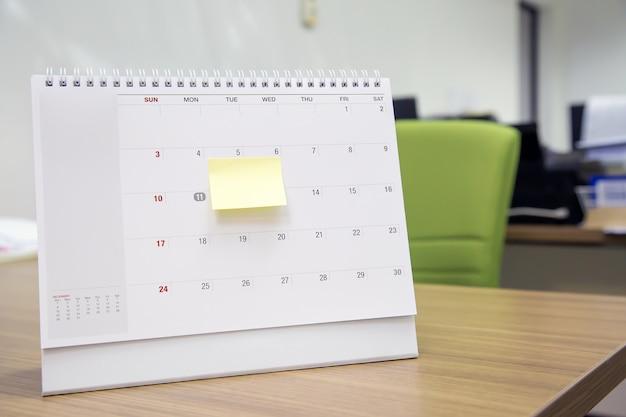 Календарь с бумажным сообщением на офисном столе для планировщика событий занят или планирует Premium Фотографии