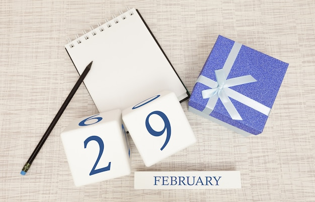 Calendar with trendy blue text and numbers for february 29 and a gift in a box. Premium Photo