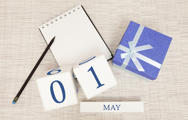 Calendar with trendy blue text and numbers for may 1 and a gift in a box. Premium Photo