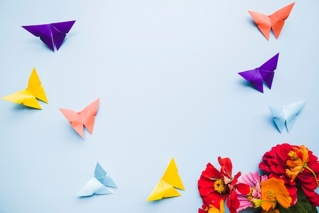Calendula marigold flowers and origami paper butterflies on blue background Free Photo