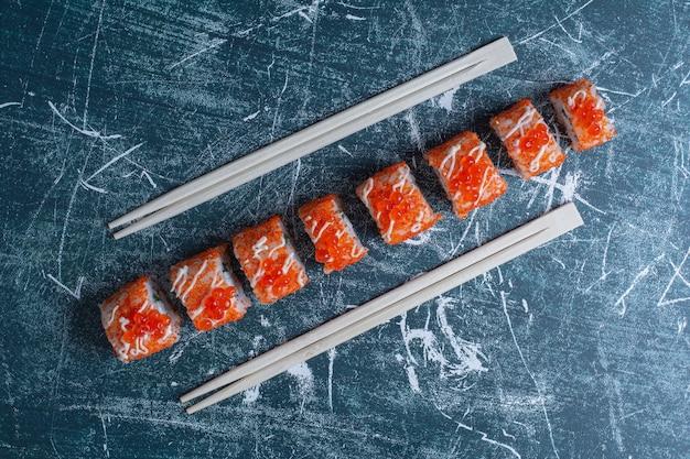 青に赤キャビアを箸で飾ったカリフォルニアロール。 無料写真