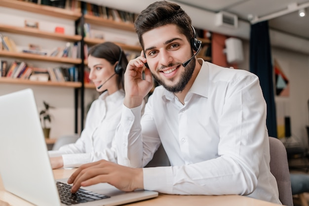 Человек работает оператором поддержки call-центра с гарнитурой на ноутбуке Premium Фотографии